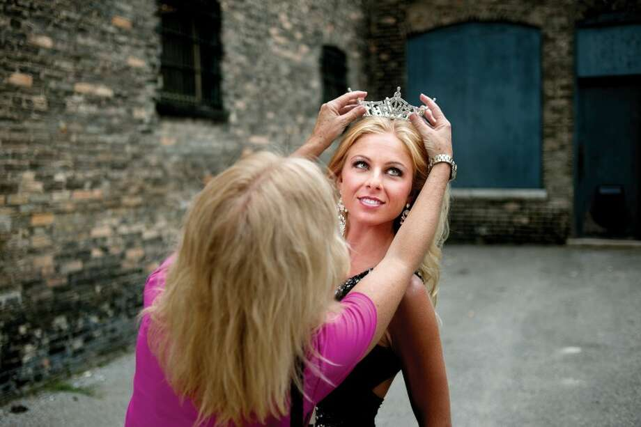 THOMAS SIMONETTI | tsimonetti@mdn.net Miss Bay County Sydney Learman, right, of Linwood has a crown put atop her head by her mother Lindsay Learman in an alley in Downtown Bay City on Friday during a photo shoot. Learman, previously Miss Auburn/Midland, gives up her crown on July 23. Photo: THOMAS SIMONETTI | Tsimonetti@mdn.net