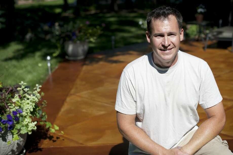 Joe Waskevich of Waskevich Contracting poses in front of a stained concrete deck he just finished at a Midland home. Photo: THOMAS SIMONETTI | Tsimonetti@mdn.net