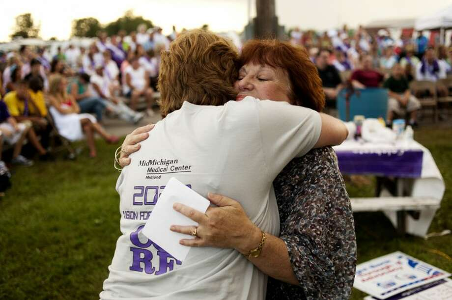 Joan Herbert of Midland, left, embraces Linda Dielman of Mt. Pleasant after Dielman spoke at the Survivor/Caregiver Ceremony at Relay for Life of Midland County on Saturday evening. Dielman talked about caring for her husband, Everett Dielman, in his final days with cancer. He passed away in 2009. The 24 hour relay started at 9 a.m. on Saturday morning and teams stayed up through the night walking to fight back against cancer. Photo: NEIL BLAKE | Nblake@mdn.net