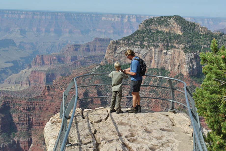 A father and son get a close look at the Grand Canyon. Photo: STEVE GRIFFIN | For The Daily News