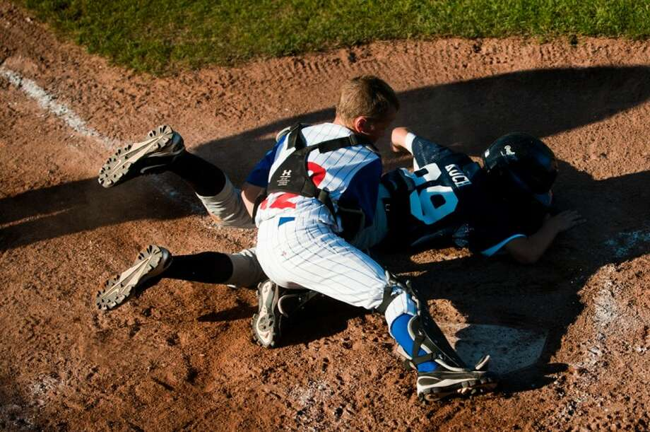 NEIL BLAKE | nblake@mdn.netNortheast catcher Logan Walko tags out Fraternal Northwest baserunner Brenden Kuch during the game on Thursday at Wilson Field at Northeast Little League.