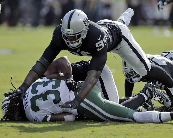 Aldon Smith (99) leaps in to help finish the tackle on Chris Ivory (33) in the first quarter as the Oakland Raiders played the New York Jets at O.co Coliseum in Oakland, Calif., on Sunday, November 1, 2015.