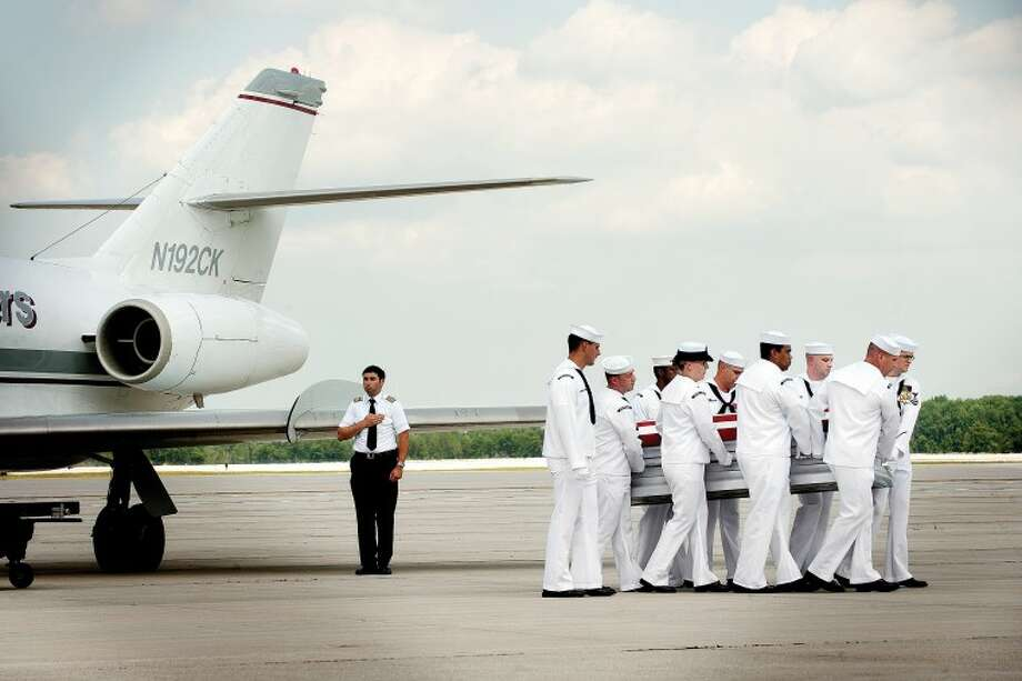 """A ceremonial guard of eight Navy hospital corps sailors led by a petty officer first class carry the casket containing the body of U.S. Navy Hospital Corpsman Aaron """"Doc"""" Ullom, of Midland, Mich., from the plane to a waiting hearse Tuesday, July 19, 2011 at the MBS International Airport in Freeland, Mich. The hearse was then escorted from the airport to the Ware-Smith-Woolever Funeral Home in Midland, Mich. Photo: THOMAS SIMONETTI 