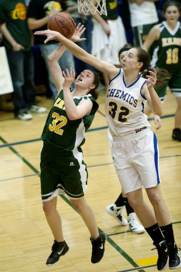 Midland's Maura Mcafee, right, blocks a shot by Dow's Josie Queary during the third period Friday at Midland High School. Midland won the district championship 44-29. Photo: NICK KING | Nking@mdn.net