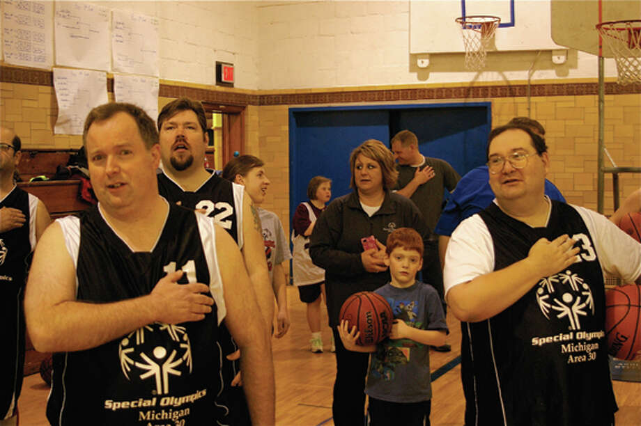 Midland County Special Olympics basketball skills athletes Rex Fritz (foreground, left), Brandon LaJoice (jersey number 22) and Pete Roseberry (right) join other athletes, volunteers and spectators in the Pledge of Allegiance to the U.S. flag and republic at an annual tournament hosted by the Area 30 (Midland County) Special Olympics organization Friday night at MidlandÕs Central Middle School.