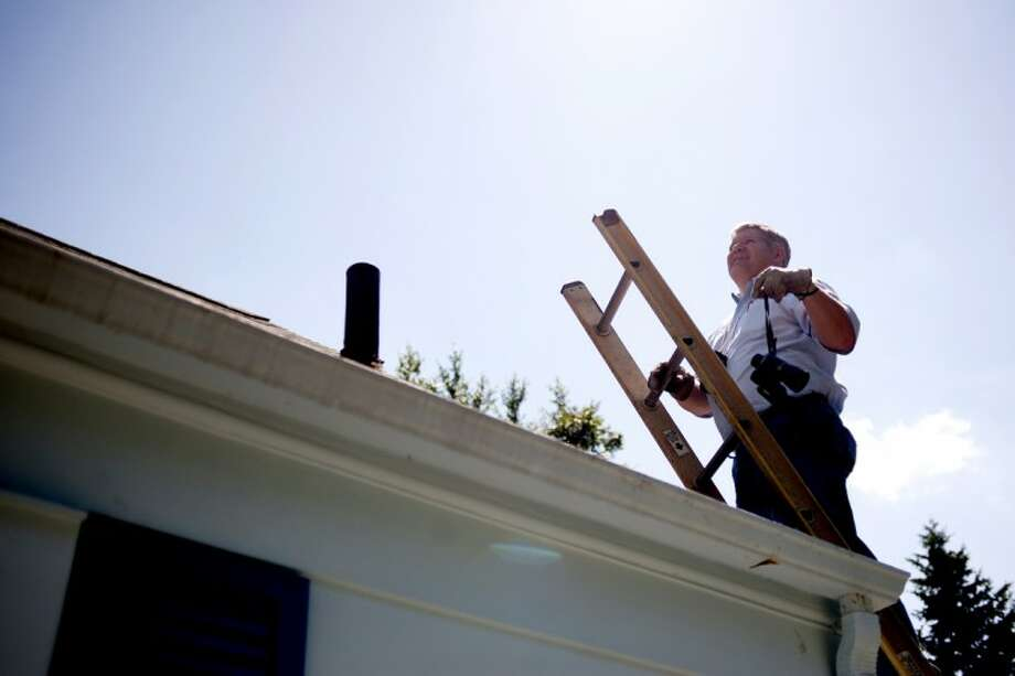 John Spencer of Sherlock Home Inspectors Inc. examines the roof of a Midland home on Thursday. Spencer says he follows a checklist covering structural components of the home, as well as electrical systems, HVAC and plumbing. Photo: THOMAS SIMONETTI | Tsimonetti@mdn.net