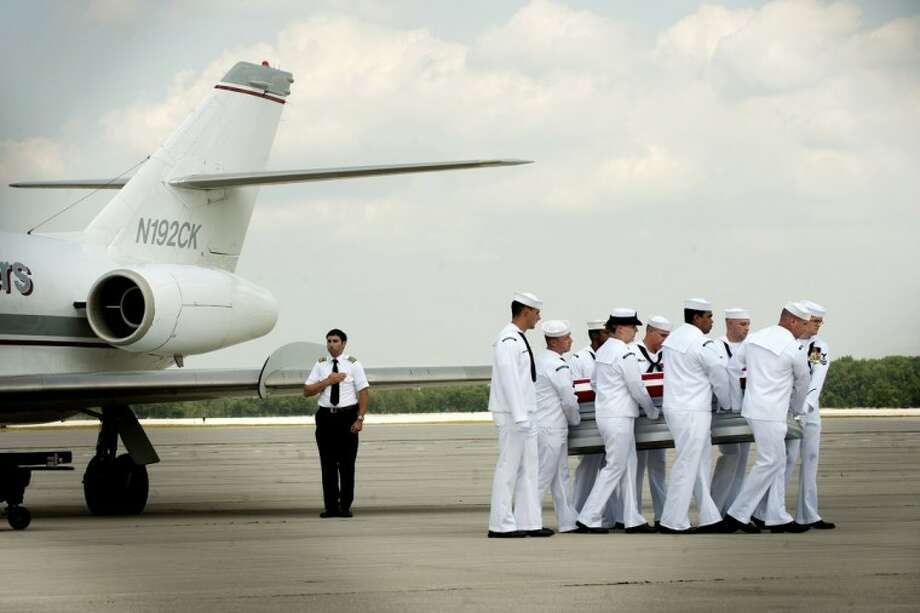 "The casket containing the body of U.S. Navy Hospital Corpsman Aaron D. ""Doc"" Ullom is carried from the plane on Tuesday at MBS International Airport to be returned to Midland. Photo: By Thomas Simonetti"