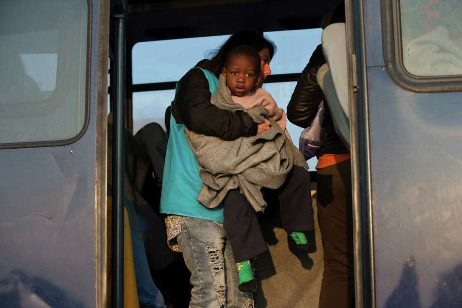 A worker with the United Nations refugee agency takes a toddler onto the bus heading to the Moria camp, after he and others were rescued off the coast of the Greek island of Lesbos, on Monday. The U.N. removed its workers on Tuesday. Photo: Petros Giannakouris, STF / AP