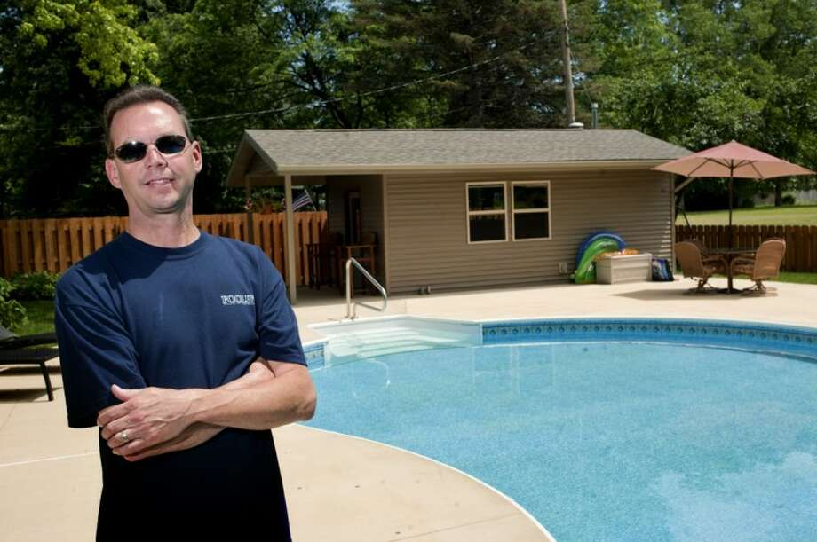 Midland Pool and Recreation President Todd Hayward poses near a pool he installed for the Baker family in Midland. Hayward said that in-ground pools are popular in Michigan and has already installed 6 with more to work on so far this year. Photo: NICK KING | Nking@mdn.net