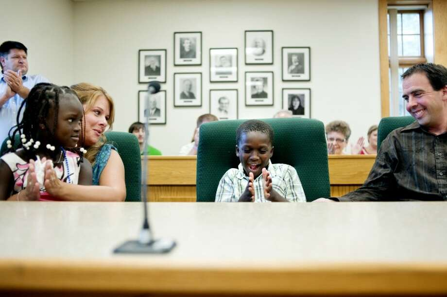 From left, Elmise, Jessica, Armon and Rob Archer celebrate after adoption proceedings in front of Midland County Probate and Family Court Judge Dorene  Allen Wednesday at the Midland County Courthouse. The Archers have been trying to adopt the Haitian children, Elmise and Armon, since 2008. Family and friends crowded the courtroom to watch the children legally become a part of the Archer family. Photo: NICK KING | Nking@mdn.net