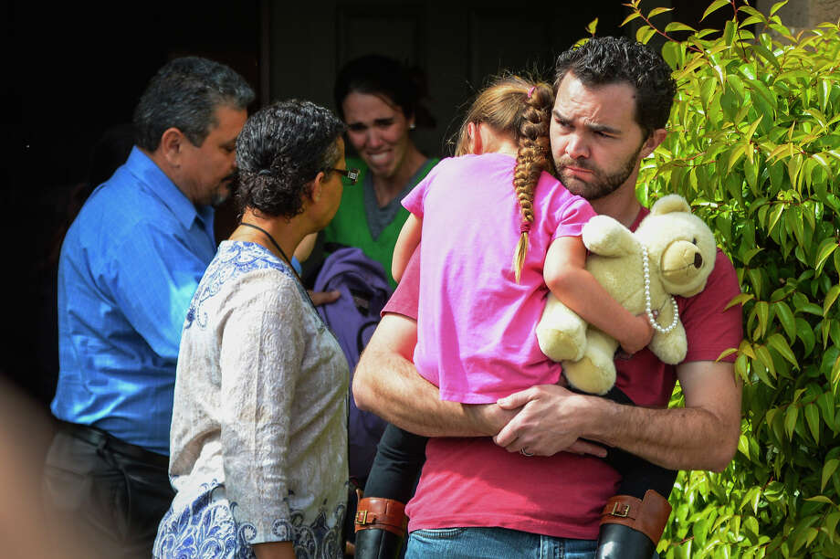 Members of family services arrive to take Lexi away from her foster parents Rusty Page, who carries her, and Summer Page, who cries in the background, on Monday in Santa Clarita, Calif. Photo: David Crane, MBR / Los Angeles Daily News