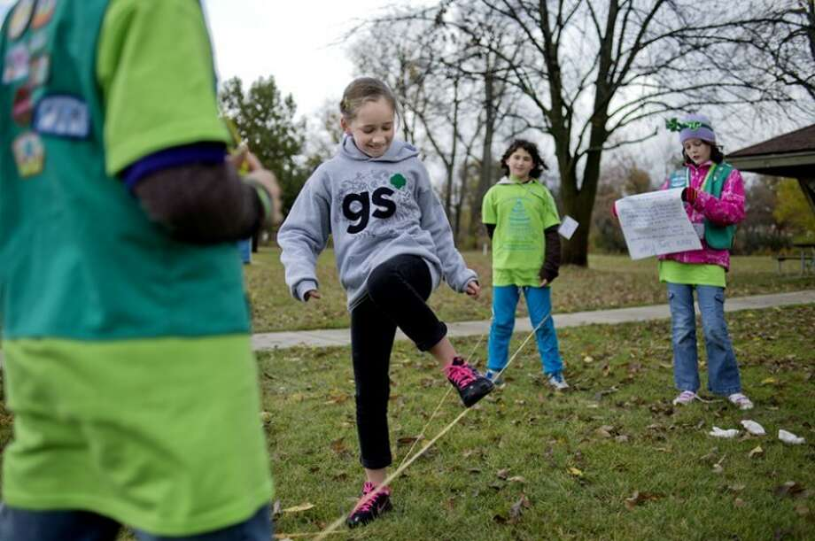 NICK KING | nking@mdn.net Girl Scout Shianne Shores, 10, of Belleville, center, plays Chinese jump rope with Midland Girl Scouts, from left, Emilia Bruce, 10, Grace DeMoville, 10, and Abigail Hnizda, 10, Saturday at Chippewassee Park. Girl Scouts participated in various game and activities at the park including wall climbing, disc golf and Chinese jump rope, to name a few. Girl Scouts from across Michigan came to Midland to celebrate the birthday of founder Jiliette Gordon Low. Events were held at Heritage Park, Emerson Park, Chippewasse Park, Chippewa Nature Center, and Dow Gardens.