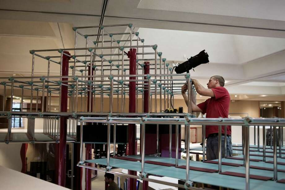 SEAN PROCTOR | photo@mdn.netJustin Herline, of Hemlock, an employee with Thomas Trombley Electric, installs a light fixture on an exhibit in the Hall of Ideas at the Midland Center for the Arts. The permanent exhibition is currently being renovated. Photo: Sean Proctor