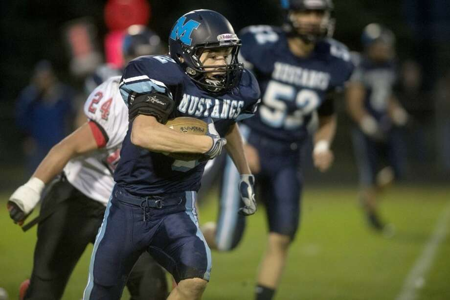 NEIL BLAKE | nblake@mdn.netMeridian's Jacob Wenzlick runs the ball during the game against Beaverton at Meridian High School on Friday. For a photo gallery of the game, click on the yellow photo gallery link. Photo: Neil Blake/Midland  Daily News