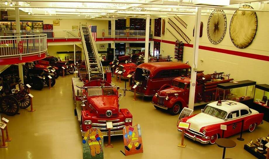 This view shows some of the vehicles recently exhibited in the Michigan Firehouse Museum in Ypsilanti, plus life nets on the wall at right. In front of the 1964 open-cab Kalamazoo aerial ladder truck, with a siren in its hood, are two firefighter figures. Visitors can stand behind the figures to pose for photographs.