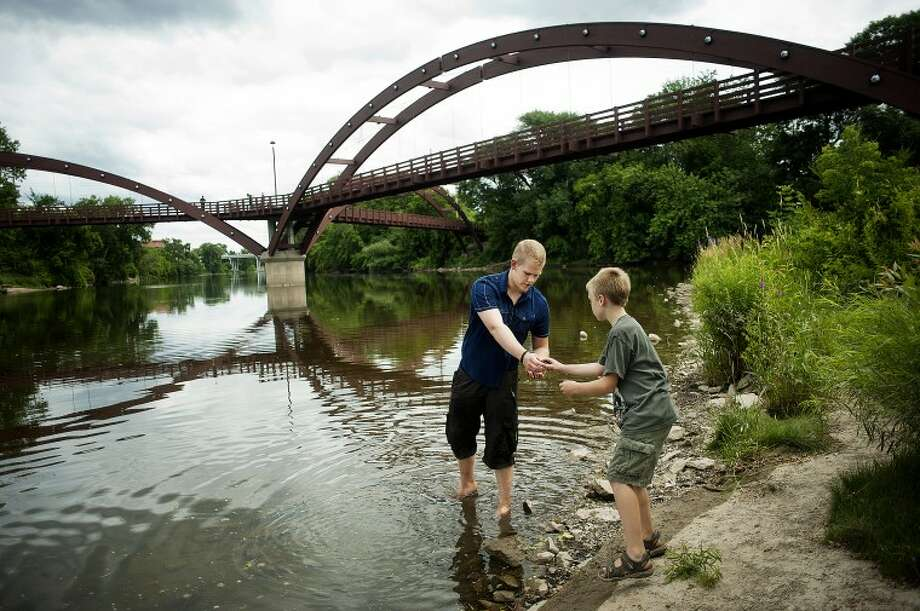 NEIL BLAKE | nblake@mdn.netParker Wheeldon, 18, of Midland, passes Tommy McQuiston, 8, of Midland, a few rocks to skip as they explore the riverbank near the Tridge on Thursday. Wheeldon's girlfriend, Jama Tobey, 17, of Midland, looks after Tommy and his younger brother Alex, 5, during the summer and the four of them spent the afternoon in the park. Photo: Neil Blake