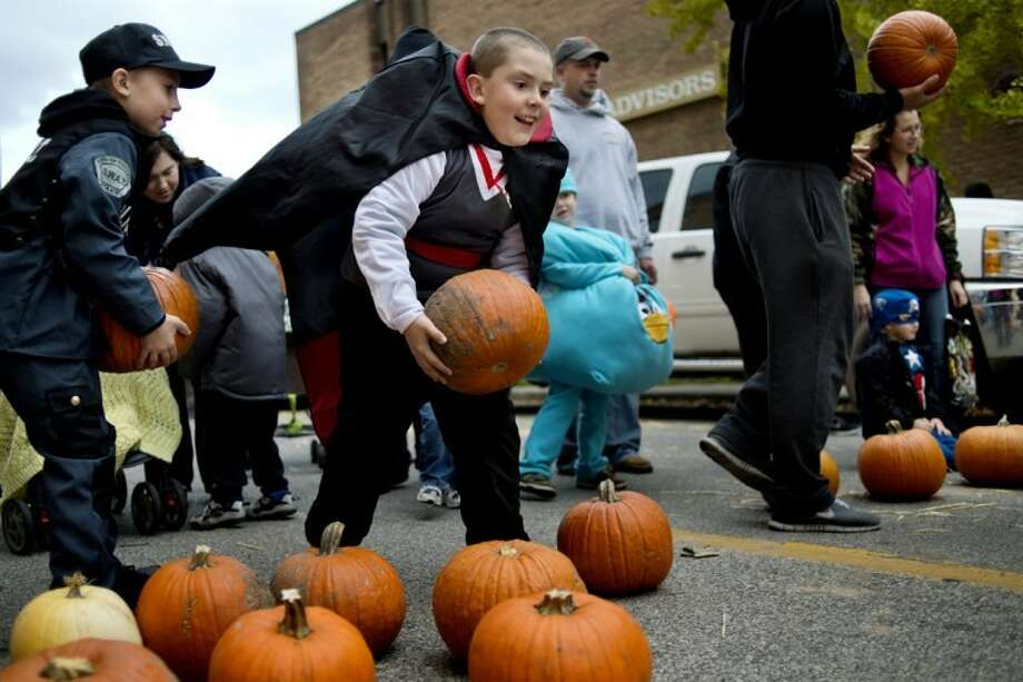 NICK KING | nking@mdn.netTrevor Newton, 10, right, dressed as Dracula, hurls a pumpkin down McDonald Street as friend Mani Mesh, 10, dressed as a SWAT team member, prepares his pumpkin at the pumpkin rolling station during the 2012 Pumpkin Festival Thursday on Main Street. Grandma's Pumpkin Patch and Downtown Midland presented the event that featured family-friendly events like pumpkin rolling and bowling and decorating, hay rides, trick or treating and a donut eating contest, to name a few. Photo: Nick King/Midland  Daily News