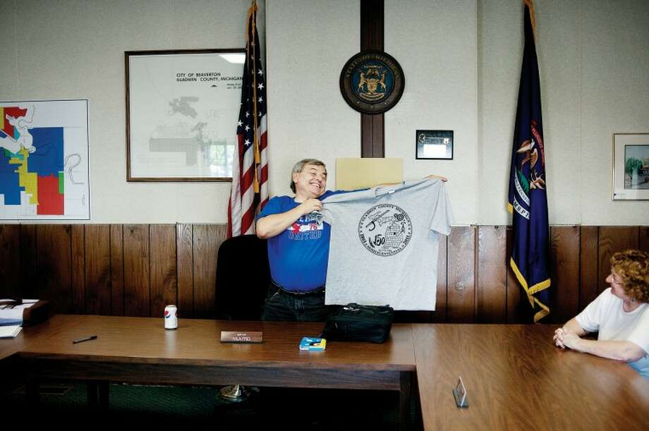 NICK KING | nking@mdn.netBeaverton Historical Society President Bob Frei holds up a shirt commemorating the Gladwin County First Settler Sesquicentennial Celebration during a meeting about the upcoming 150-year celebration at Beaverton City Hall. Photo: Thomas Simonetti
