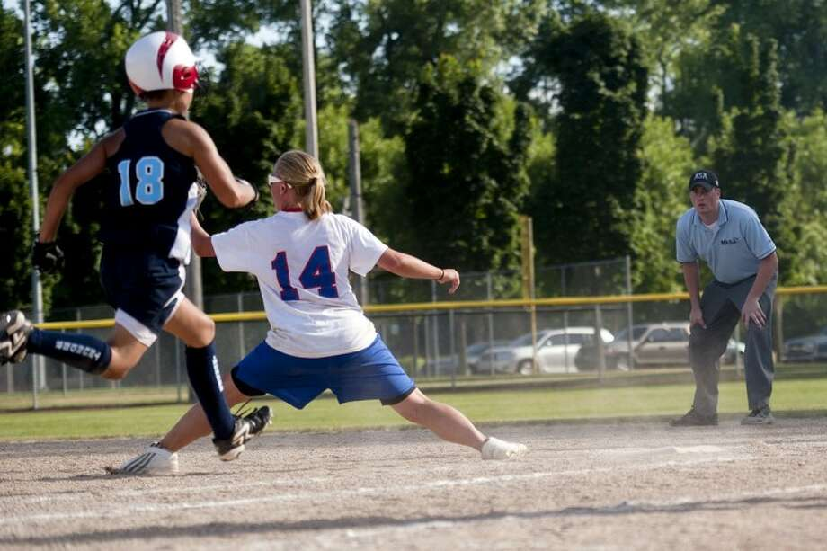 SARA WINKLER | for the Daily NewsJessica Chatterton of the Lady Explorers stretches out in order to snag a catch at first base and make an out on Karrie Jaynes of Pinconning out during a game Saturday evening at Currie Stadium in Emerson Park.
