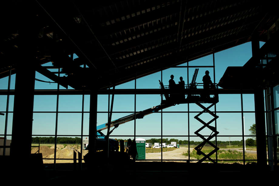 Construction crews continue work on the new MBS International Airport terminal on Tuesday. The new terminal, which is set to open next year, will replace the current one that was built in 1965. Photo: NEIL BLAKE | Nblake@mdn.net  / Midland Daily News | Neil Blake