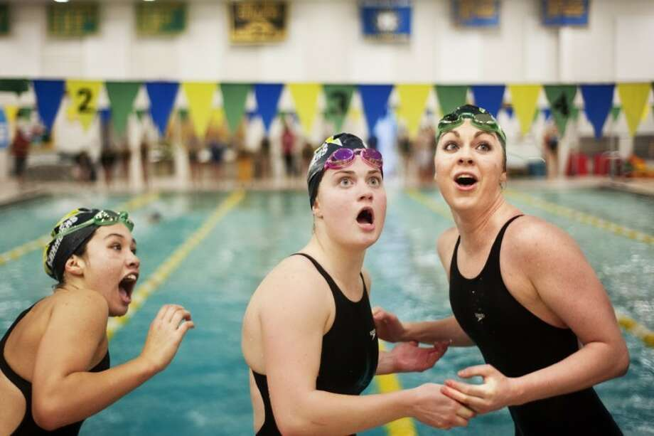 Zack Wittman | for the Daily NewsDow High swim team members, from left, Julia Ahrns, Julie Shirk, and Emily Maraskine look at the time board and gasp as their relay partner, Kara Dean, completes the anchor leg to break the pool record for the 200 yard medley relay in their meet against Midland High on Thursday. For 20 photos from the meet, click on the yellow photo gallery link.