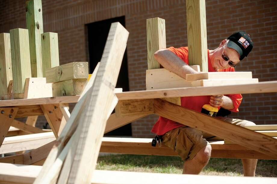 THOMAS SIMONETTI | tsimonetti@mdn.netDave Kelly, a millwork specialist with Home Depot, builds legs for a picnic table bench on Thursday at the West Midland Family Center. Kelly was one of about 80 people volunteering at the center to build 50 tables and 50 benches. Photo: Thomas Simonetti/Midland  Daily