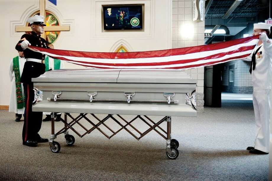 "A United States flag is draped over the coffin of U.S. Navy Hospital Corpsman Aaron D. ""Doc"" Ullom on Friday following an afternoon service at the Midland Evangelical Free Church in Midland. His body was later buried at the Midland Cemetery. Photo: THOMAS SIMONETTI 