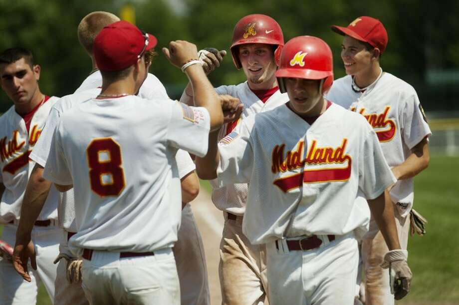 Midland Berryhill's Lars Cronkright, center, is congratulated by his teammates on his home run against Gladwin during the American Legion State Championship game at Northwood University on Saturday. Photo: NEIL BLAKE | Nblake@mdn.net