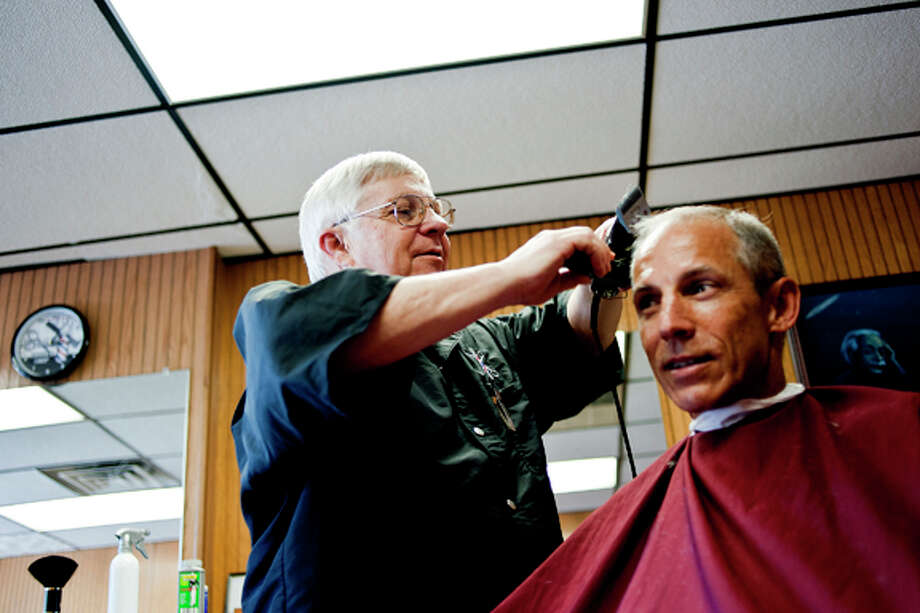 "Local barber Larry DuFort of Midland uses clippers to give regular customer Keith Richardson of Auburn a haircut  Wednesday afternoon at Rita's Family Barber Shop. DuFort is celebrating his 50th year on the job. ""I'll retire when I die,"" DuFort said. ""I'm not in any hurry. I enjoy it too much."" Photo: SARA WINKLER 