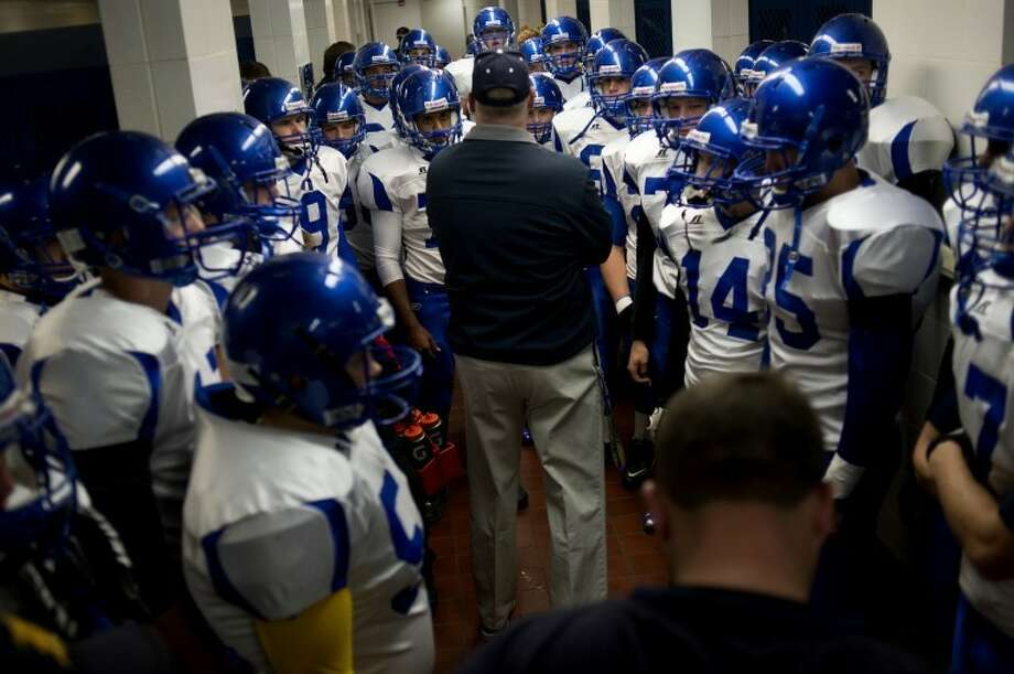 NEIL BLAKE | nblake@mdn.net The Midland varsity football team surrounds head coach Eric Methner in the locker room at Bay City Western before the game on Friday. The Chemics won against the Warriors 42-14 making them 8-0 on the season. Next week they face cross city rivals H.H. Dow High. Photo: Neil Blake/Midland  Daily News