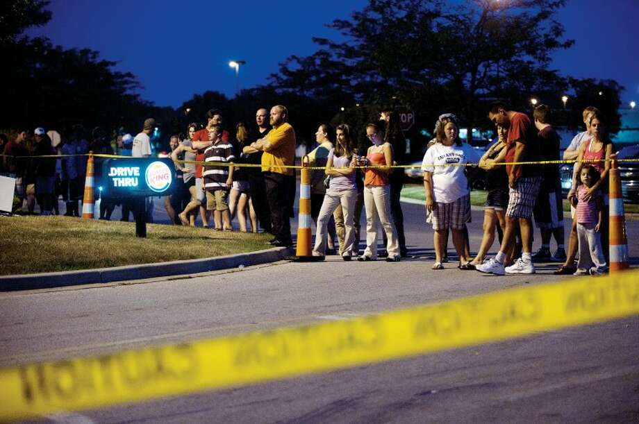 People line the police tape at the Burger King on Eastman Avenue in Midland where a man was fatally shot on Monday. Photo: NEIL BLAKE | Nblake@mdn.net