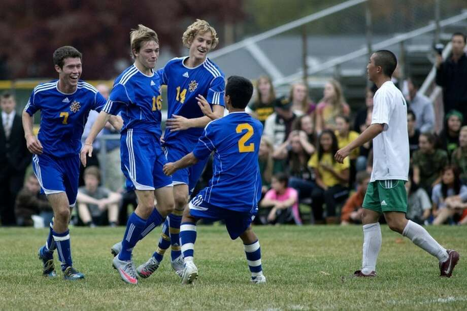 NICK KING | nking@mdn.netMidland's Charles Wakeman (16) celebrates his goal with teammates, from left, Nathan Foura, Tyler Sowels and Justin Johnson during the second half Wednesday at Dow High School. Dow's Kei Yamamoto, right, looks on. The Chemics won 3-0. For more photos, click on the yellow gallery link. Photo: Nick King/Midland  Daily News