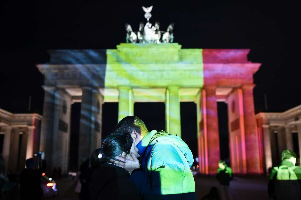 A couple embraces as the colors of the Belgian flag are projected on to the Brandenburg Gate in Berlin as the German capital shows its solidarity following the Brussels attacks on March 22, 2016.