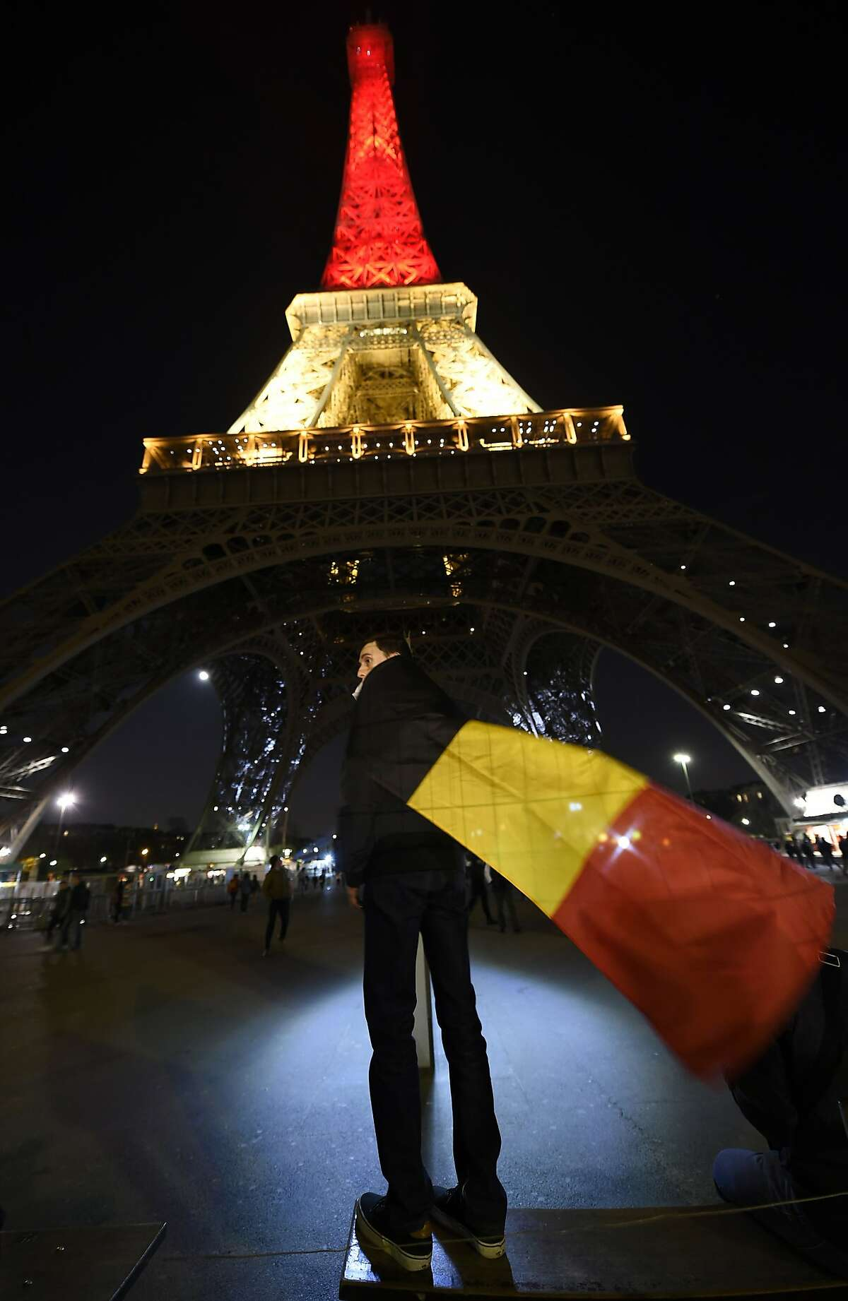 A boy wearing a Belgian flag stands under the Eiffel Tower in Paris illuminated in colours of the Belgian flag.