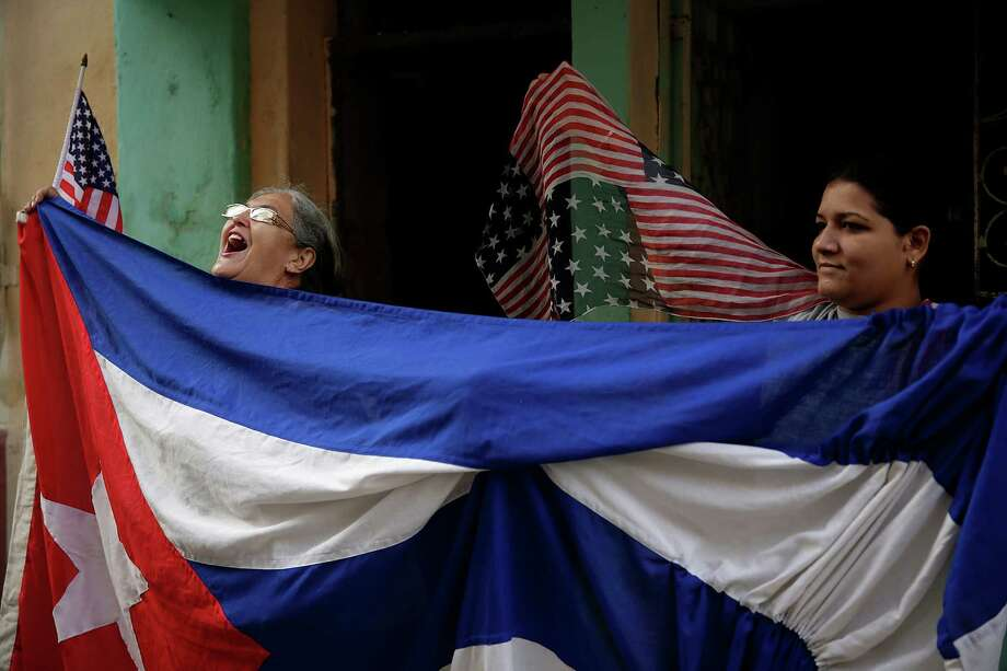 Maria Castro, left, and Laritza Mojenas demonstrate their enthusiasm for President Barack Obama's visit from the front door of her Central Havana home on Tuesday. (Robert Gauthier/Los Angeles Times/TNS) Photo: Robert Gauthier, MBR / Los Angeles Times