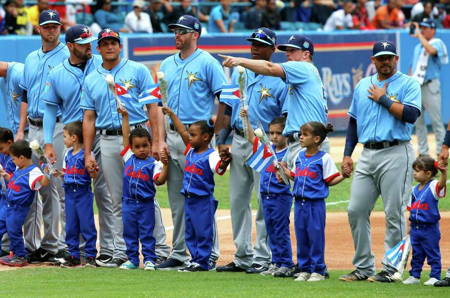 Generations and nations intermingle as Cuban children join the Tampa Bay players before the Rays' 4-1 victory over Cuba on Tuesday. Photo: Al Diaz, MBR / Miami Herald