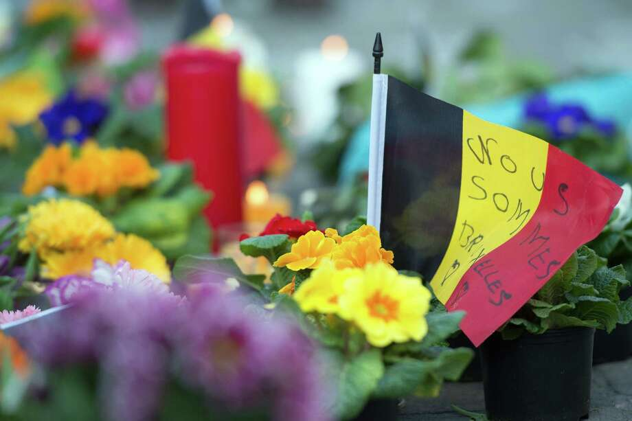 ''Nous sommes Bruxelles'' (We are Brussels) is written on a small Belgian flag next to flowers and candles outside the stock exchange at Place de la Bourse in Brussels on Tuesday. (Federico Gambarini/DPA/Zuma Press/TNS) Photo: Federico Gambarini, MBR / Zuma Press