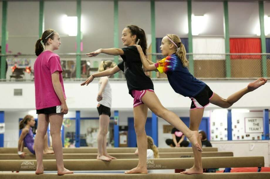 "JEFFREY SMITH | for the Daily NewsMidland residents Peyton Gerstacker,12, right, balances with Gwynne Ozkan, 12, as Rylie Johnstone, 12, watches during a ""Pink Out"" portion of a fundraiser Friday evening at the Midland Gymnastics Training Center. Johnstone competed in the Flip for a Cure meet over the weekend to benefit the Elsa U. Pardee Foundation for cancer treatments and support. ""I've been training, it's fun,"" Johnstone said."