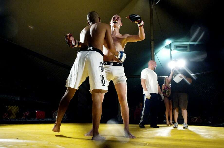 NEIL BLAKE | nblake@mdn.netNano Smith, left, gets a hug from Zachary Spanke after the fight was called when Smith broke Spanke's nose during the mixed martial arts cage fight at the Auburn Cornfest on Thursday. Photo: Neil Blake/Midland  Daily News
