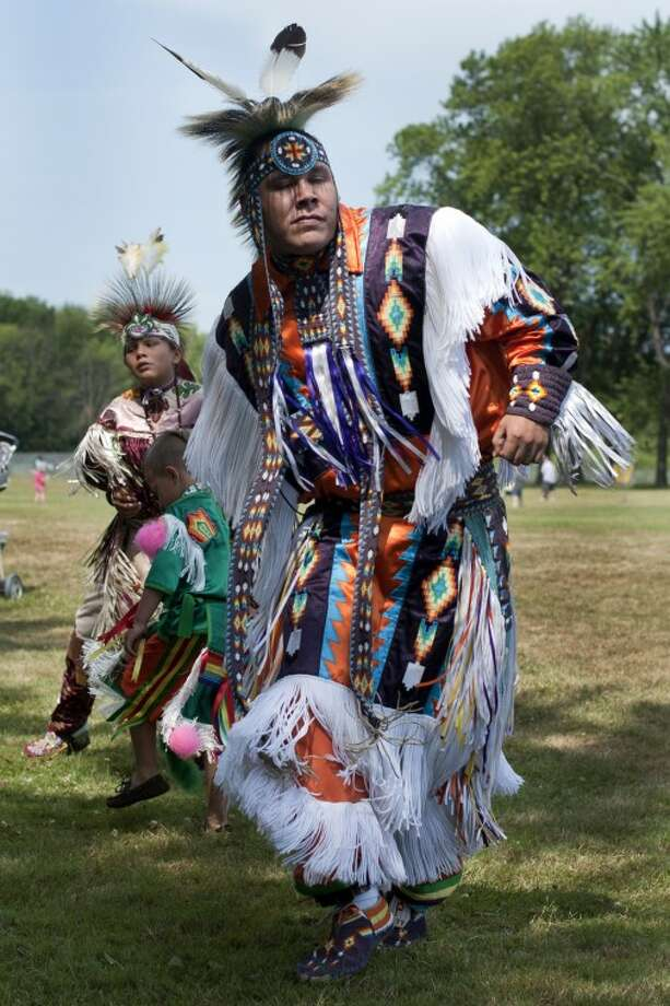 BRITTNEY LOHMILLER | blohmiller@mdn.net Miengun Pamp of Mt. Pleasant leads the men from the Ziibiwing Center in the Grass dance during the American Indian Dance Presentation at Chippewassee Park Saturday afternoon. Photo: Brittney Lohmiller