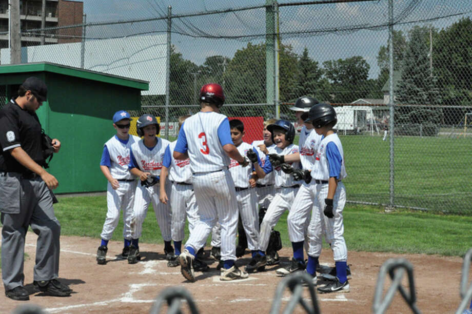 Northeast's Jeff Landis (3) is congratulated by his teammates as he crosses home plate after hitting a three-run homer in the third inning of Monday's game against North Saginaw Township at the 10-11-year-old Little League Baseball state tournament in West Branch. Photo: Photo By Brian Carroll