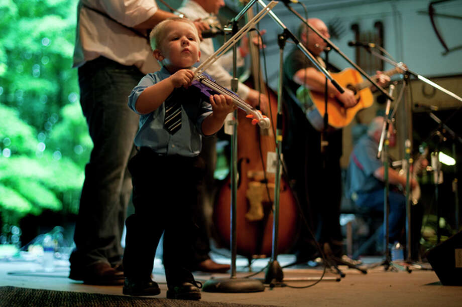 "NEIL BLAKE | nblake@mdn.net Gavin Conley, 3, plays a toy fiddle as his grandfather John Coffey performs in the band Pushin the Limits at the Salt River Bluegrass Festival on Friday. This is the festival's 34th year. ""Many people have grown up here,"" said Kris Carr, festival organizer. ""And now they bring their kids."" The festival continues throughout the day today at Salt River Acres in Shepherd. Photo: Neil Blake/Midland  Daily News / Midland Daily News"