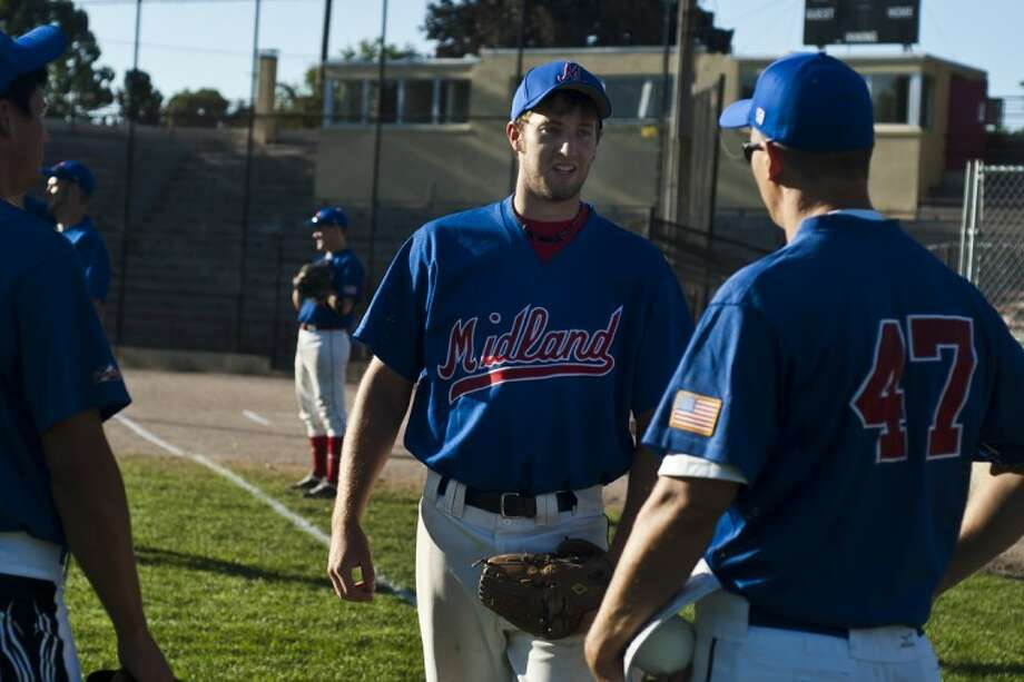 Lathan Goumas | for the Daily NewsJon Gwizdala of the new Midland Junior Explorers' fastpitch softball team talks to a coach before a game in Midland against the USA Junior National Fastpitch Team last Friday. The Junior Explorers will play in the ISC 21-and-under Tournament in Midland in August. Photo: Lathan Goumas