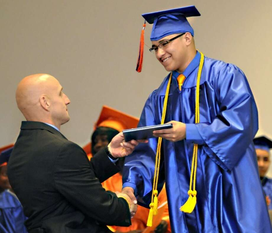 AP Photo | The Saginaw News, Jeff SchrierIn this June 21 photo, Raymond Buitron Jr., the 2012 valedictorian of Saginaw Learn to Earn Academy, accepts his diploma from Principal Gomoluch during a commencement ceremony at Saginaw ISD Transitions Center in Saginaw Township. Buitron graduated with a 3.6 grade point average and was given the Turnaround Achievement Award and a $1,000 scholarship. He will use that money when he starts classes at Delta College in the fall. Photo: Jeff Schrier