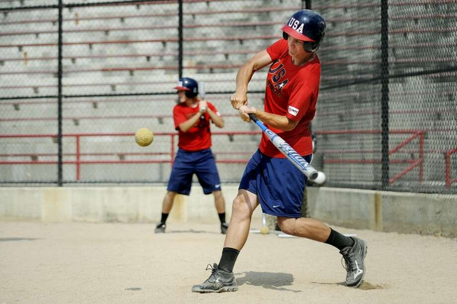 NICK KING | nking@mdn.netTyler Johnson, of Union, Mo, takes a swing at a ball during batting practice Monday during the USA Softball Men's Junior National Team's workout at Currie Stadium at Emerson Park. The team is currently touring Michigan, and Midland is one of its stops. Photo: Nick King/Midland  Daily News