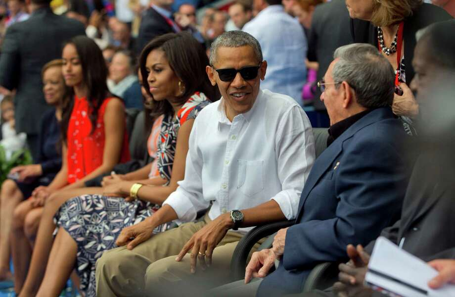 President Barack Obama, with his family, talks with Cuban President Raul Castro at an exhibition baseball game Tuesday in Havana between the Tampa Bay Rays and the Cuban national team. Photo: Pablo Martinez Monsivais, STF / AP