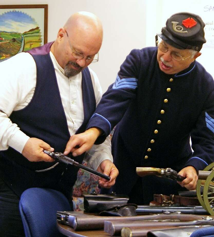STUART FROHM | for the Daily NewsBob Rostollan, left, of Auburn, and Tom Cherry, of Geneva Township, discuss authentic and replica Civil War weapons at the senior citizens center in Sanford Tuesday. Cherry spoke on the 4th Michigan Infantry Regiment's participation in some Civil War battles. He is the elected commander of a Michigan unit of the North-South Skirmish Association. Its members competitively fire original and reproduced Civil War handguns, long guns and artillery. Rostollan and other members of The Rostallons musical group performed at the center.