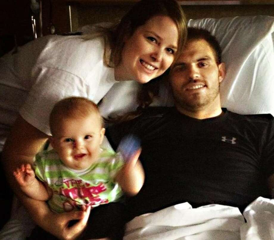 In an undated photo provided by the Mills family, Travis Mills is seen in his hospital bed with his wife, Kelsey, and daughter, Chloe, at the Walter Reed National Military Medical Center in Bethesda, Md. Photo: HOEP