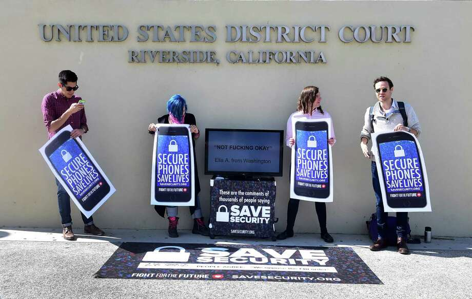 """L-R:Activists Luis Nolasco, Aki Rose, Evan Greer and Josh Rabb hold placards reading """"Secure Phones Saves Lives"""" during a protest in front of the US District Court in Riverside, California, on March 22, 2016.  The US government's decision to delay its effort to force Apple to help unlock an attacker's iPhone may only postpone the inevitable drawn-out battle over encryption and data protection. / AFP PHOTO / FREDERIC J. BROWNFREDERIC J. BROWN/AFP/Getty Images Photo: FREDERIC J. BROWN, Stringer / AFP or licensors"""
