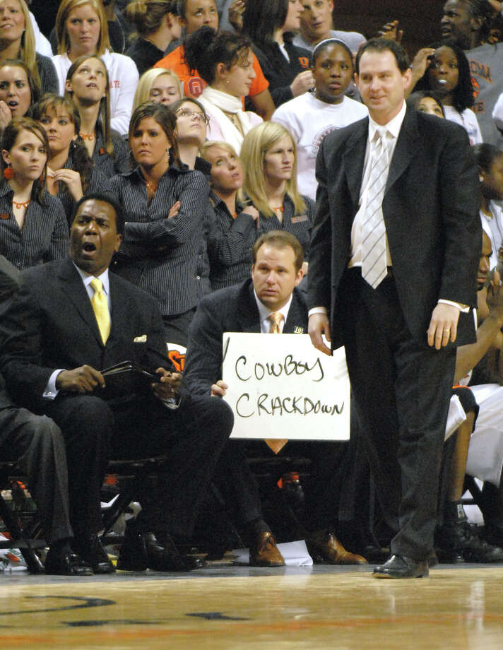 Oklahoma State assistant coach Kyle Keller, center, flanked by assistant coach Jimmy Williams, left, and head coach Sean Sutton, right, holds up a whiteboard for Oklahoma State players during overtime of an NCAA college basketball game in Stillwater, Okla., Tuesday, Jan. 16, 2007. Oklahoma State defeated Texas in triple overtime 105-103.(AP Photo/Brody Schmidt) Photo: BRODY SCHMIDT / STR